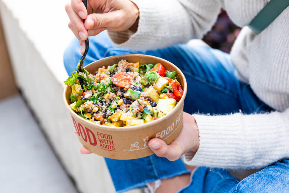 Woman eating a salad from B.GOOD