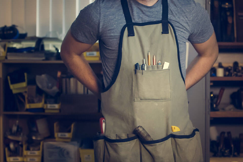 Man wearing apron with tools