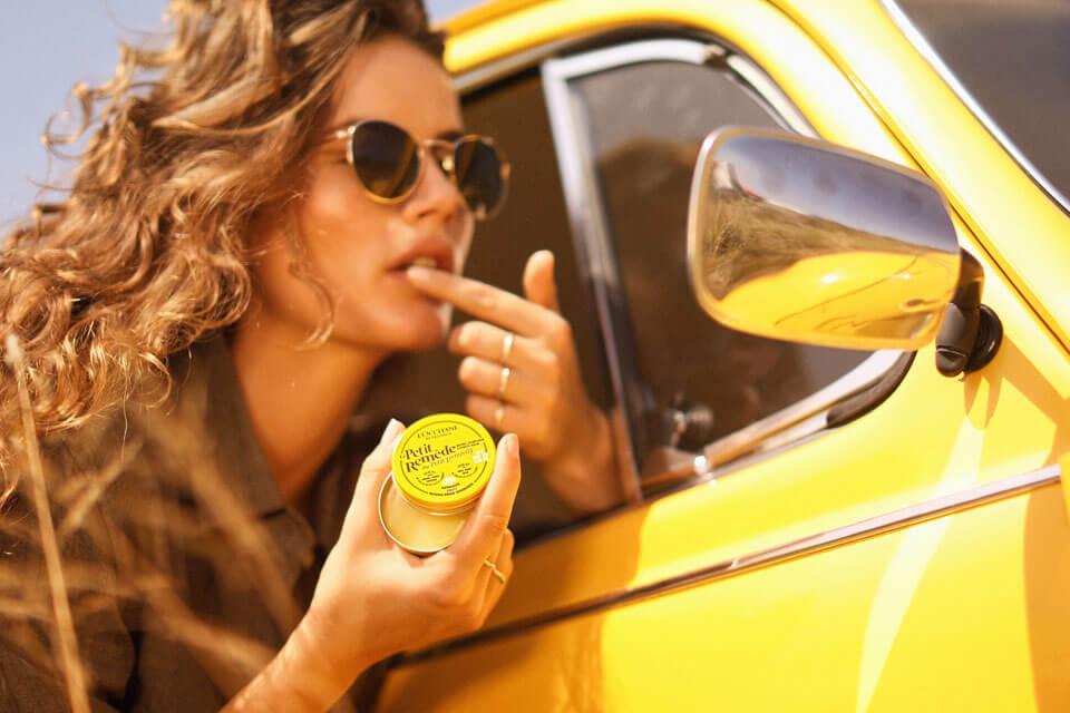 Woman applying lip balm in car mirror