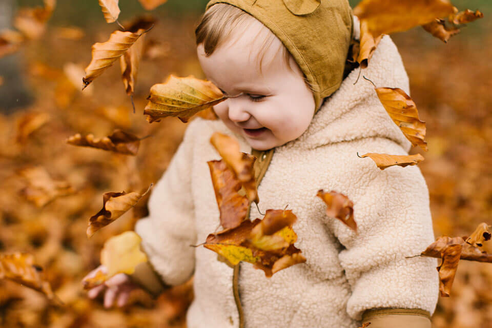 Small child in fall leaves