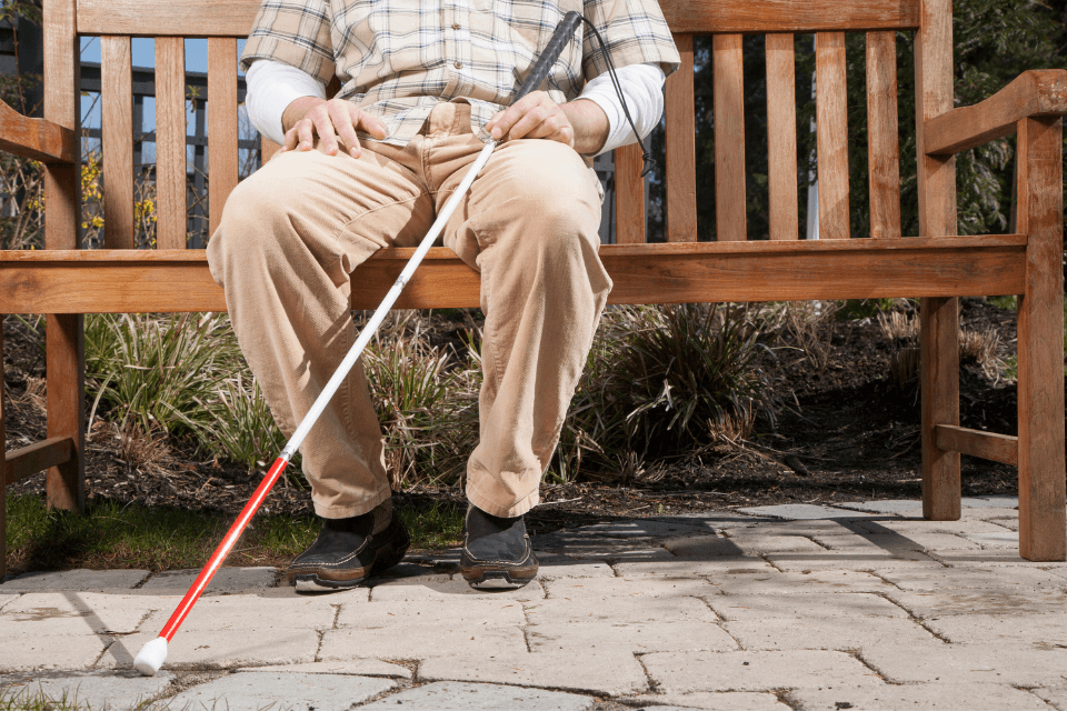 Man sitting on bench with white cane.